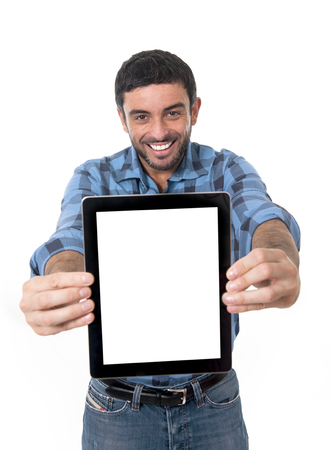 young attractive man holding and showing blank digital tablet with copy space  in social network,  blog , internet community and communication concept wearing casual shirt and jeans smiling happy isolated on white background  photo