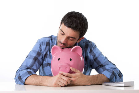 kaput: young attractive broke man worried in stress feeling sad hugging empty pink piggy bank in bad financial situation concept wearing casual shirt isolated on white background Stock Photo