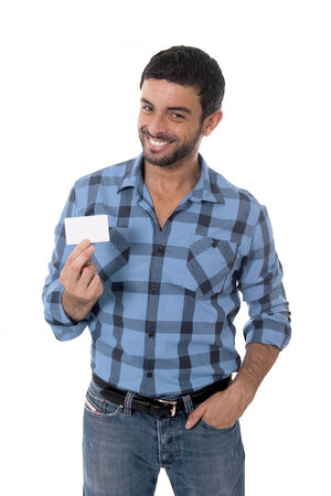 logo marketing: young attractive man in casual shirt and jeans showing and pointing blank business card smiling happy isolated on white background having copy space to add in the card with branding logo or marketing text