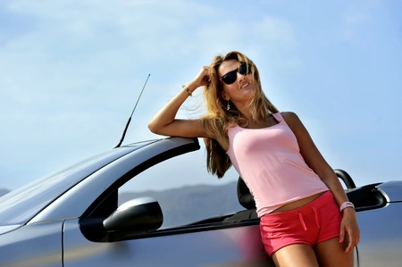 chic woman: young sexy chic woman with sunglasses leaning on cabrio sport car in relax on the beach summer holidays having a sunbath in front of the sea Stock Photo