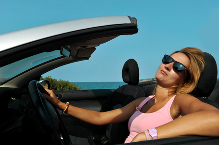 young sexy chic woman with sunglasses driving cabrio sport car in relax on the beach  having fun on summer holidays at the beach  photo