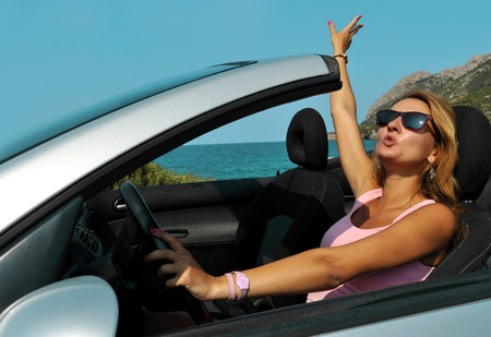 Driving: young sexy chic woman with sunglasses driving cabrio sport car in relax on the beach  having fun on summer holidays at the beach  Stock Photo