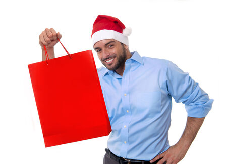 consumerism: happy young attractive man wearing Santa hat holding and pointing red shopping bag in christmas consumerism