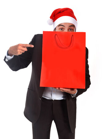 happy attractive business man wearing Santa hat and suit holding and pointing red shopping bag in christmas consumerism  photo