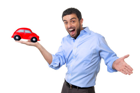 young happy attractive man pointing big red toy car on his hand isolated on white background in vehicle insurance, new automobile buying and renting concept photo