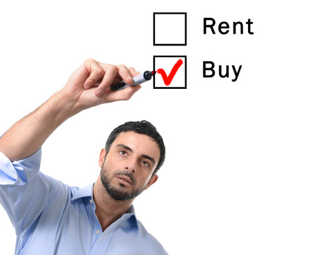 financial questions: young handsome business man choosing rent or buy option at formular ticking buying box with red marker on glass isolated on white background in housing, real estate and property owner concept Stock Photo