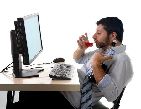 intoxicated: young alcoholic business man drinking whiskey sitting drunk at office with computer holding glass of alcohol looking depressed and in crisis wearing loose tie in addiction problem concept isolated white background