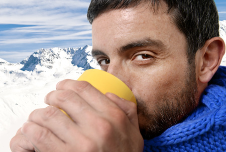 young attractive man outdoors drinking cup of coffee or tea in cold winter warming his hands with the mug wearing blue scarf on snow mountains at Christmas holidays photo