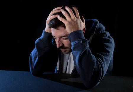 jonge wanhopige man leed pech met de handen op het hoofd in een diepe depressie, pijn en emotionele stoornissen, verdriet en wanhoop concept geïsoleerd op zwarte achtergrond met en edgy en grunge studio verlichting Stockfoto