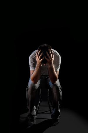 jonge wanhopige man die lijden en die het gezicht met de handen in een diepe depressie, pijn en emotionele stoornissen, verdriet en wanhoop concept geïsoleerd op zwarte achtergrond met en edgy en grunge studio verlichting