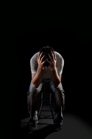 desperation: young desperate man suffering and covering face with hands in deep depression , pain and emotional disorder, grief and desperation concept isolated on black background with and edgy and grunge studio lighting