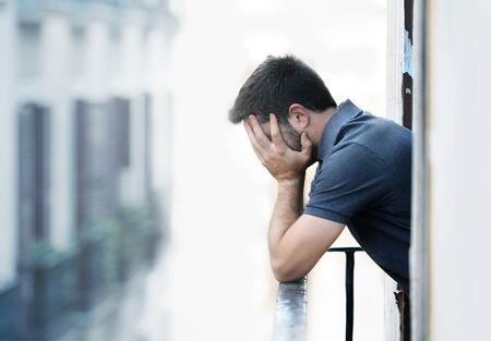 Eenzame jonge man buiten in het huis van een balkon op zoek depressief, vernietigd, verdrietig en lijden emotionele crisis en verdriet op een stedelijke achtergrond
