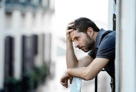 pensando: Hombre joven sola fuera en la casa balc�n mirando deprimido, destruido, triste y sufre crisis emocional y el dolor en un fondo urbano Foto de archivo