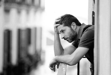 hombre solitario: Hombre joven sola en la casa fuera balc�n con aspecto deprimido, destruido, triste y sufrimiento emocional crisis y la pena pensar en tomar una decisi�n de vida dif�cil e importante en un fondo urbano en blanco y negro