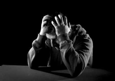 young desperate man suffering with hands on head in deep depression, pain , emotional disorder, grief and desperation concept isolated on black background with grunge studio lighting in black and white Stock Photo