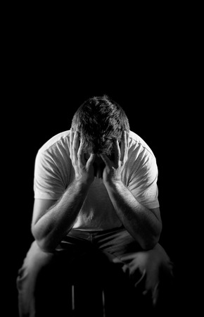 young desperate man suffering with hands covering face in deep depression, pain , emotional disorder, grief and desperation concept isolated on black background with grunge studio lighting in black and white photo