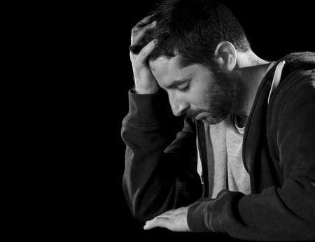 hombre solo: hombre desesperado joven que sufre con la mano en la cabeza en una profunda depresi�n, dolor, trastorno emocional, el dolor y la desesperaci�n concepto aislado en el fondo negro con iluminaci�n de estudio grunge blanco y negro Foto de archivo