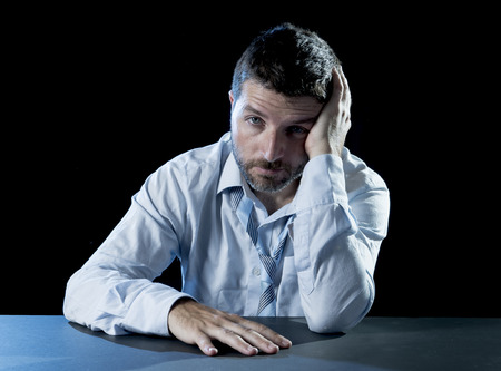 desperation: young desperate sick businessman suffering headache with hands on head in deep depression, pain , emotional disorder, grief and desperation concept isolated on black background