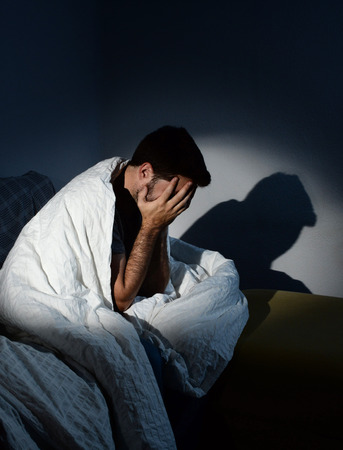 Young man sitting on couch at home wrapped in messy duvet suffering depression and emotional crisis, grieving in solitude and feeling lonely and desperate in dim light with shadow