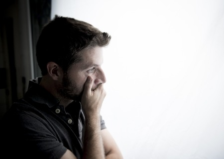 young attractive man leaning desperate on window glass at home, looking worried, depressed, thoughtful and lonely suffering depression in work or personal problems concept with copy space