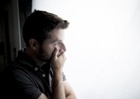 Séduisant jeune homme se penchant désespérée sur le verre de la fenêtre à la maison, l'air inquiet, déprimé, pensif et solitaire dépression souffrance dans le travail ou des problèmes personnels notion avec copie espace Banque d'images - 31417068