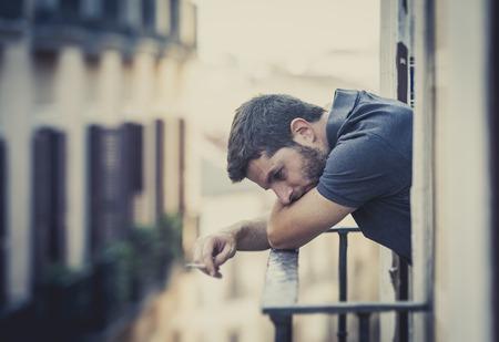 man smoking: joven solo fuera en la casa balc�n terraza fumando deprimido, destruido, perdido y triste sufrir crisis emocional y depresi�n en la urbana