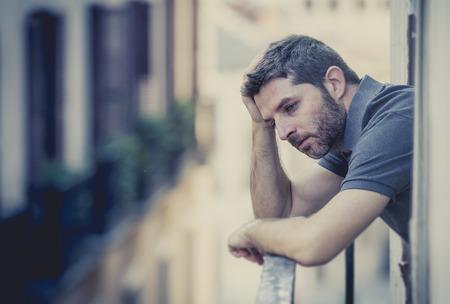 jonge man alleen buiten het huis balkon terras op zoek depressief, vernietigd, verspilde en verdrietig lijden emotionele crisis en depressie op stedelijke achtergrond Stockfoto
