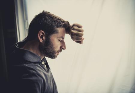 agotado: Hombre atractivo joven que se inclina desesperada en cristal de la ventana en casa, mirando preocupado, deprimido, pensativo y solitario depresión sufrimiento en el trabajo o problemas personales concepto con el espacio de la copia