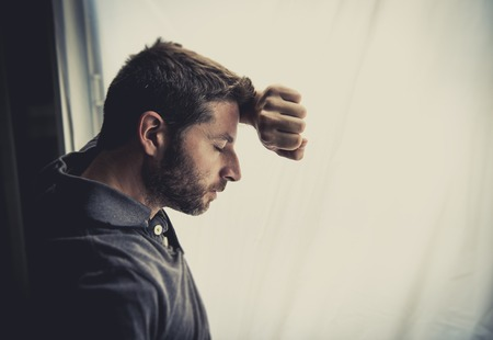 young attractive man leaning desperate on window glass at home, looking worried, depressed, thoughtful and lonely suffering depression in work or personal problems concept with copy space photo