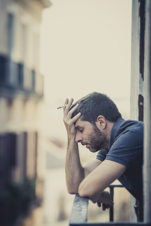 wasted: young man alone outside at house balcony terrace smoking depressed, destroyed, wasted and sad suffering emotional crisis and depression on urban  Stock Photo