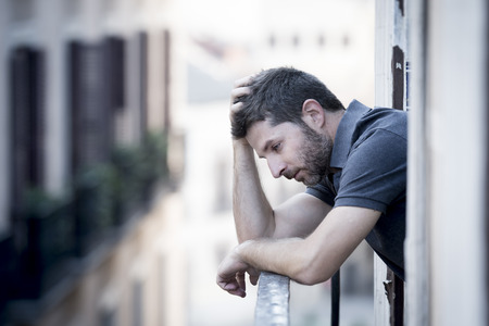 young man alone outside at house balcony terrace looking depressed, destroyed, wasted and sad suffering emotional crisis and depression  Stock Photo