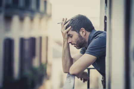 man smoking: joven solo fuera en la casa balc�n terraza fumando deprimido, destruido, perdido y triste sufrir crisis emocional y depresi�n