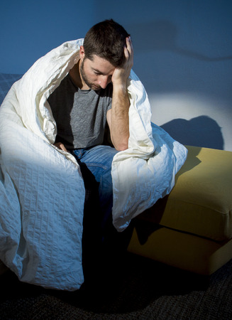 sad man alone: young sick man sitting on couch at home scary and desperate suffering insomnia, depression, nightmares, emotional crisis, mental disorder with a dim light and deep dark shadows