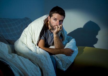 jonge zieke man zittend op de bank thuis eng en wanhopige lijden slapeloosheid, depressie, nachtmerries, emotionele crisis, psychische stoornis met een gedimd licht en diepe donkere schaduwen Stockfoto