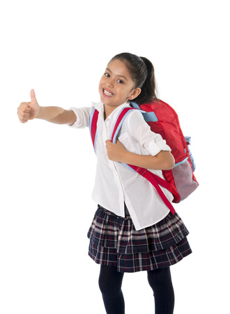 school uniform: happy sweet little school girl carrying schoolbag backpack doing ok thumb up sign in education and back to school concept isolated on white background