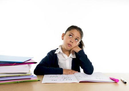 niños estudiando: dulce niño hispano mujeres estudiando en el escritorio que parece aburrida y bajo estrés que piensa con una expresión de la cara de cansancio en la educación infantil y de nuevo a concepto de la escuela aislado en el fondo blanco Foto de archivo