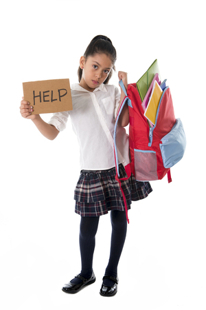 child studying: sweet hispanic little girl asking for help carrying heavy backpack or school bag full  causing her stress and pain on her back due to overweight isolated on white background Stock Photo