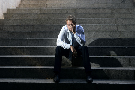 Young business man crying abandoned lost in depression sitting on ground street concrete stairs suffering emotional pain, sadness, looking sick in grunge lighting