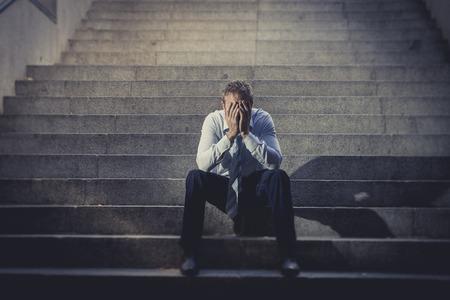 젊은 비즈니스 사람은 우울증이 그런 지 조명에서 아픈 찾고, 정신적 고통, 슬픔을 겪고 지상 거리 콘크리트 계단에 앉아 손실 포기 울고