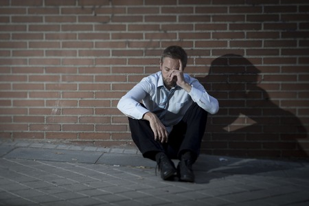 emotional pain: Hombre de negocios joven que perdi� el trabajo abandonado perdido en la depresi�n que se sienta en la esquina de la calle de tierra contra la pared de ladrillo que sufren dolor emocional, el pensamiento y llorar solo Foto de archivo