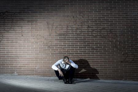 Jonge zakenman die baan verloor verlaten verloren in een depressie zitten op de grond hoek van de straat tegen bakstenen muur lijden emotionele pijn, denken en alleen huilen
