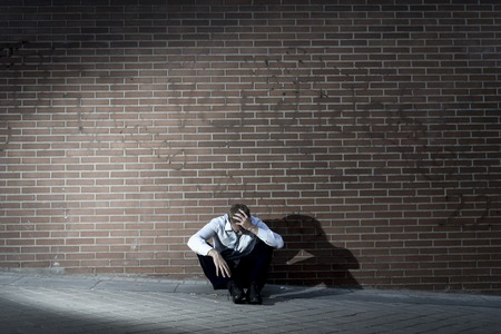 Young business man who lost job abandoned lost in depression sitting on ground street corner against brick wall suffering emotional pain, thinking and crying alone photo