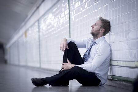 sitting on the ground: Young business man who lost job abandoned lost in depression sitting on ground street subway suffering emotional pain, thinking and leaning on wall alone