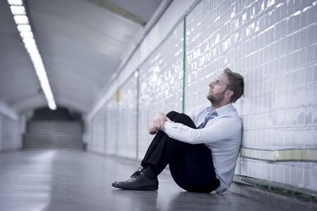 emotional pain: Hombre de negocios joven que perdi� el trabajo abandonado perdido en la depresi�n sentado en el metro de la calle de tierra que sufren dolor emocional, el pensamiento y apoyado en la pared solo