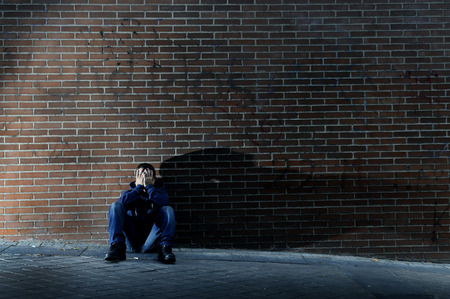 Young desperate man who lost job abandoned and lost in depression sitting on ground street corner against brick wall suffering emotional pain, crying alone in grunge lighting