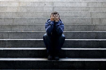 Jonge wanhopige man in vrijetijdskleding verlaten verloren in een depressie zitten op de grond straat betonnen trap alleen lijden emotionele pijn, verdriet, op zoek ziek in grunge verlichting