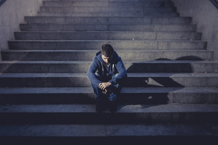 Young desperate man in casual clothes abandoned lost in depression sitting on ground street concrete stairs alone suffering emotional pain, sadness, looking sick in grunge lighting Standard-Bild