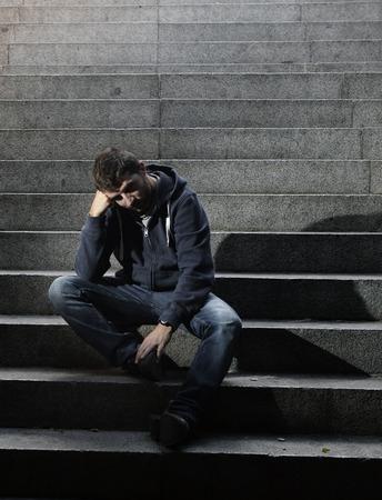 emotional pain: Hombre desesperado joven en ropa casual abandonados perdidos en la depresi�n que se sientan en la calle de tierra escaleras de hormig�n solo sufren dolor emocional, tristeza, buscando enfermos en la iluminaci�n del grunge Foto de archivo