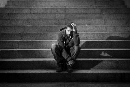sitting ground: Young desperate man in casual clothes abandoned lost in depression sitting on ground street concrete stairs alone suffering emotional pain, sadness, looking sick in grunge lighting Stock Photo