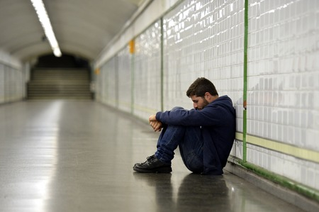 sitting on the ground: Young man abandoned lost in depression sitting on ground street subway tunnel suffering emotional pain, sadness and looking destroyed and desperate leaning on wall alone  Stock Photo